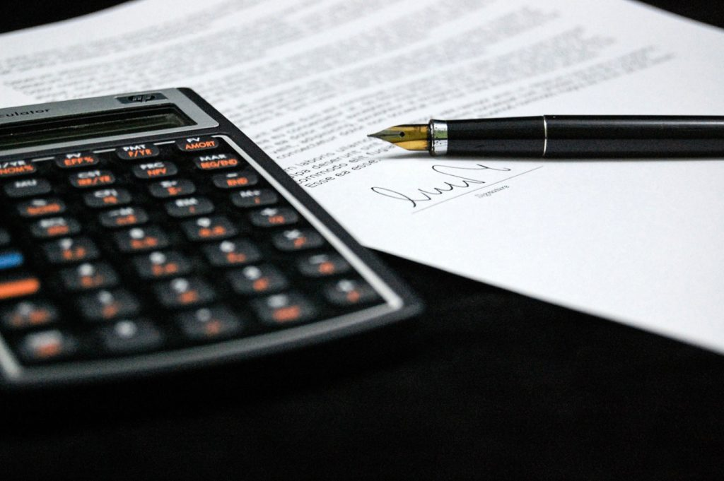 A signed contract with a pen and a calculator by the side.