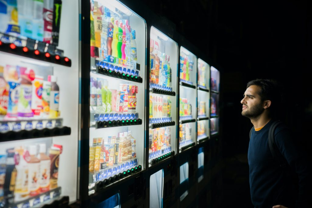 Man stares full of refreshments fridges, confused of what to choose